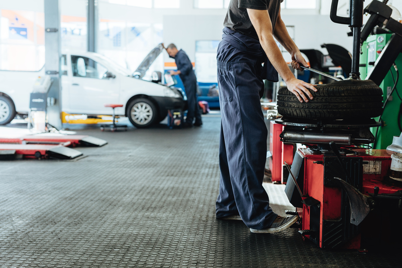 Mechanic Langport | Car repair shop with mechanics working. Mechanic replacing tire of while on machine and other inspecting a vehicle.